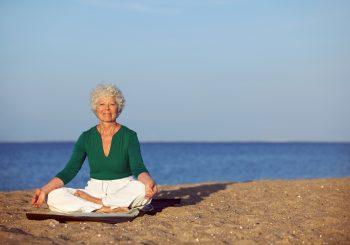 Portrait of the senior woman meditating on the seashore