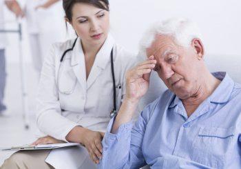 young doctor comforting a sad senior man