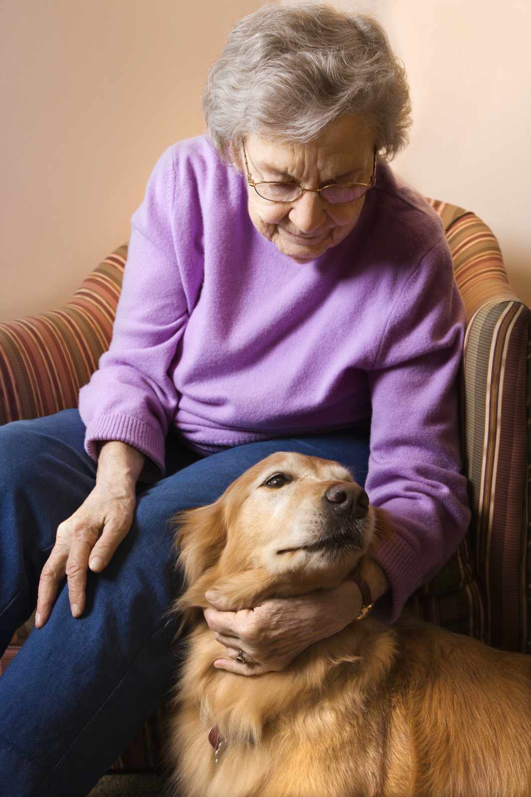 woman in bedroom at retirement community center petting therapy dog